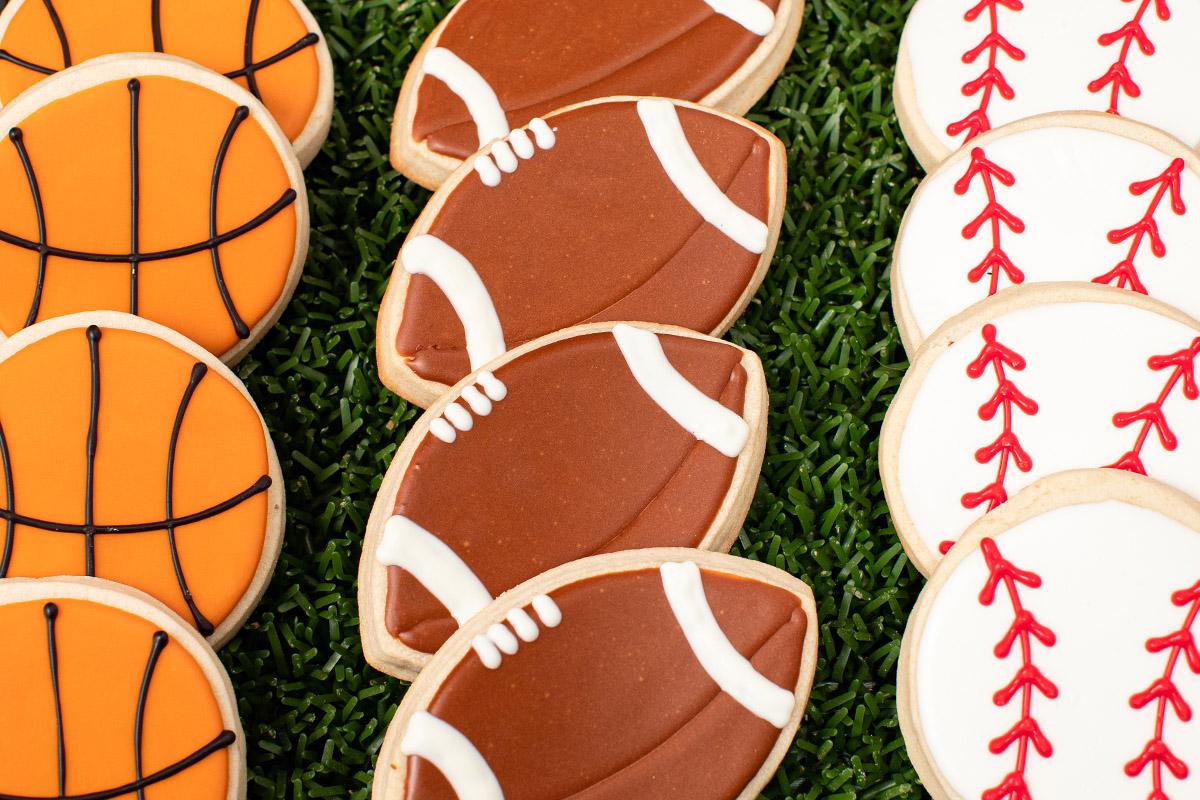 Decorate cookies of footballs, baseballs and basketballs